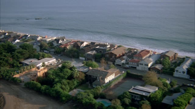 aerial over oceanfront two story and three story beach houses and mansions with tennis courts along malibu coastline. beaches. oceans. sun reflecting off water. cars driving on pacific coast highway. upper class. - 1982 stock videos & royalty-free footage