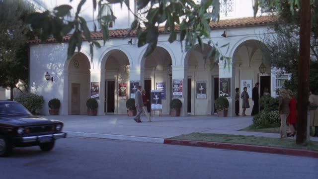 wide angle of people standing in line and walking past front of the wilshire ebell theatre with arches above entrance. could be playhouse. cars driving by on street in fg. - wilshire ebell theatre stock videos & royalty-free footage