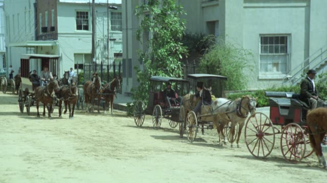 pan left to right of horse drawn carriage moving down dirt road, past carriages parked on side of road and people walking out of entrance to church with columns in front. could be in deep south. neg cuts. - carriage stock videos & royalty-free footage