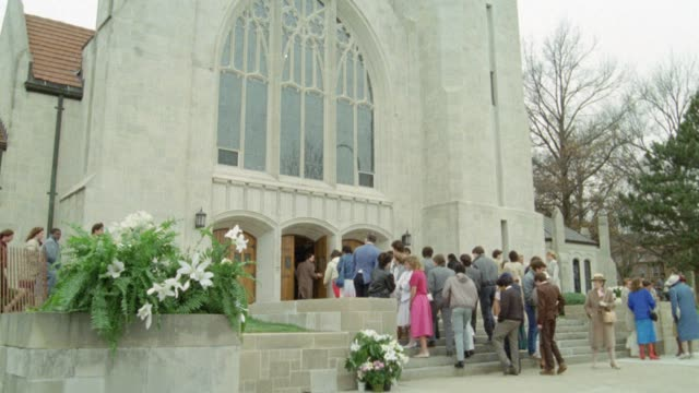 wide angle of people standing on steps in front of large church and walking through entrance. stone building. - 1985 stock videos & royalty-free footage