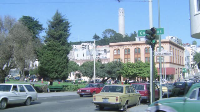pan right to left from coit tower in bg and cars driving on street in fg to saints peter and paul church with ornate steeples in north beach. people walking in washington square park in fg. could be small town. - north beach san francisco stock videos & royalty-free footage