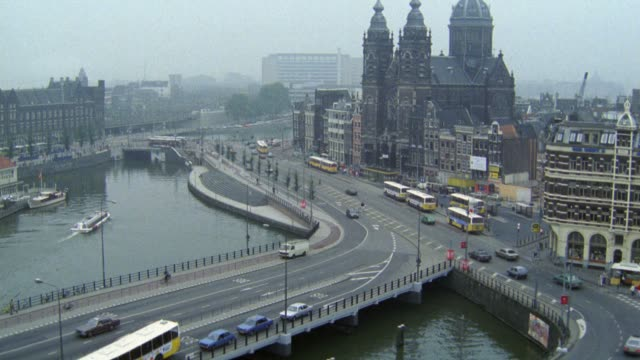 high angle down over cars and city buses driving on city streets past canal and ornate saint nicholas church. cities. europe. - 1985 bildbanksvideor och videomaterial från bakom kulisserna