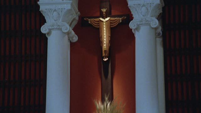 close angle of crucifix hanging on wall. columns in fg. crosses. religious. - 宗教上のシンボル点の映像素材/bロール