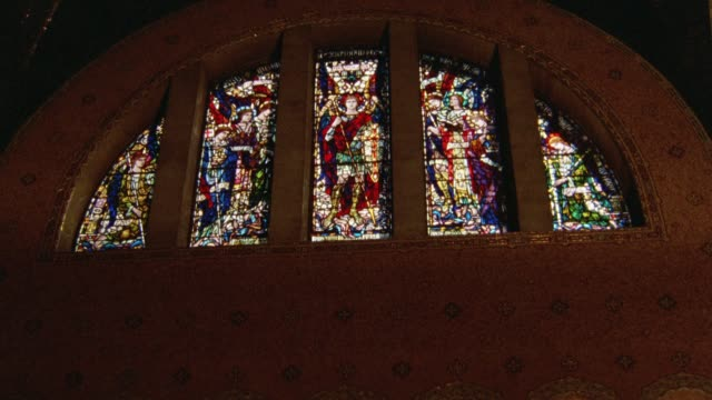 up angle of stained glass windows in church or cathedral. religious. - 美術工芸品点の映像素材/bロール
