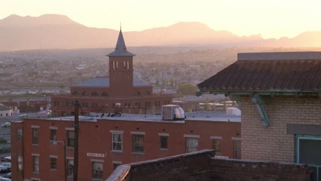 high angle down of buildings in the city of el paso texas. church steeple fg. mountains in bg. cityscapes. cities. - kirchturmspitze stock-videos und b-roll-filmmaterial