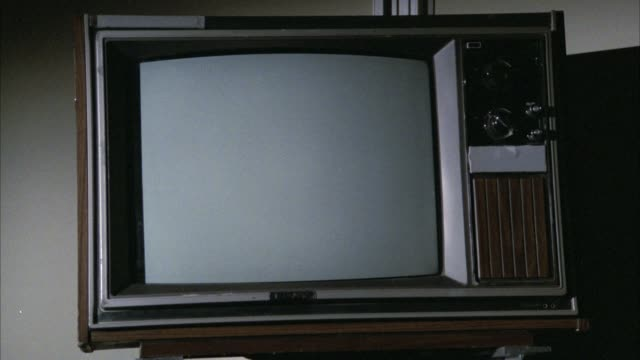 close angle of faux-wood paneled television with dials. mounted to wall. could be in hospital. - anno 1983 video stock e b–roll