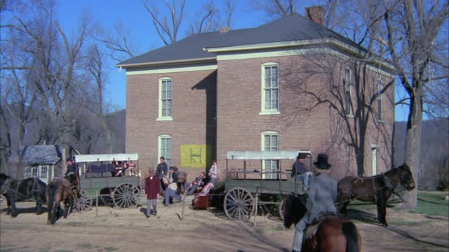 wide angle of two story brick building, could be hospital. civil war soldiers. horse-drawn carriages. bare branches of trees. - 四輪馬車点の映像素材/bロール