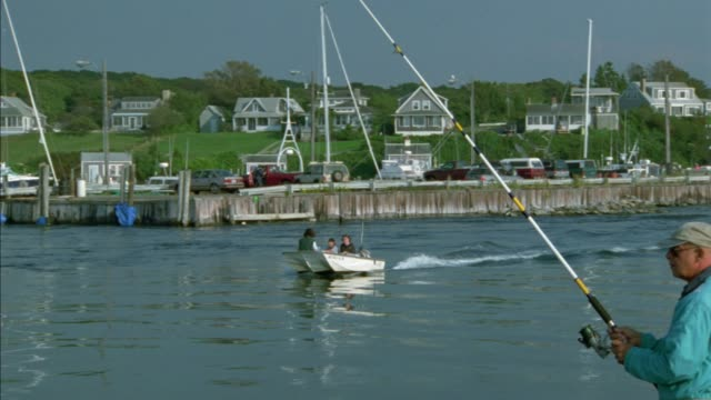 medium angle of man fishing in fg. small boat moves from right to left in channel of harbor. upper class shingle style new england houses on hills in bg. martha's vineyard. waterfront. - eastern usa stock videos and b-roll footage