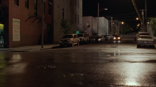 pan right to left as lincoln town car drives down street through commercial area. street lamps. could be small town. street slick with water. red suburban parked on street. matches 2002-029 lincoln town car. - lincoln town car stock videos and b-roll footage