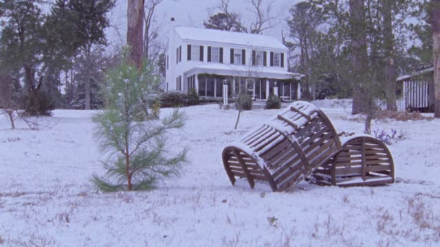 est wide angle two-story house in snow. two wooden crates, lobster or crab traps in fg. - zweistöckiges wohnhaus stock-videos und b-roll-filmmaterial