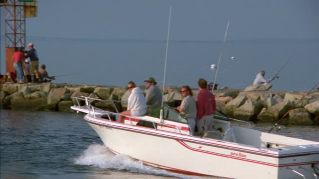 pan left of motorboat with people going fishing. rocky jetty in bg. harbor. martha's vineyard. new england. - eastern usa stock videos and b-roll footage