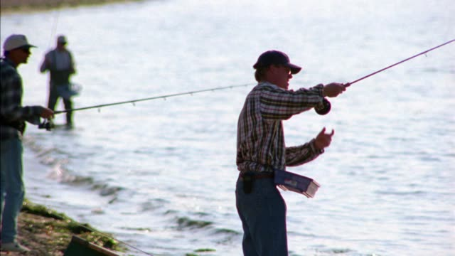 medium angle of man fishing from shore. two other men are fishing in bg. ocean. beach. martha's vineyard. new england. - ostamerika stock-videos und b-roll-filmmaterial