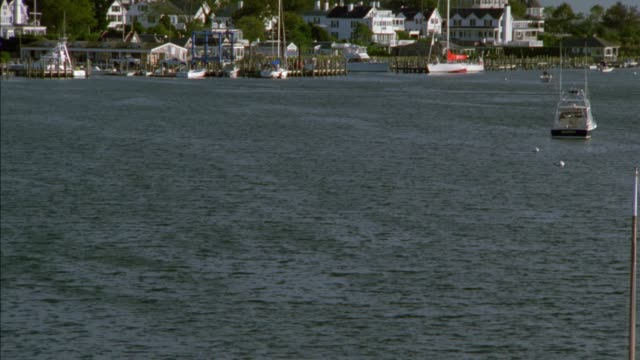 pan up from water to boats moored and anchored in harbor. upper class two story new england houses on hillside of shoreline in bg. martha's vineyard. new england coastal town. - zweistöckiges wohnhaus stock-videos und b-roll-filmmaterial