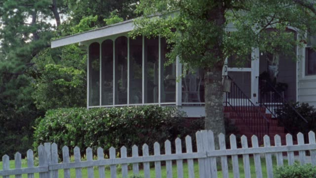 wide angle of screened in porch of two story house. white picket fence in foreground. middle class. countryside or rural area. matching dx/nx clips 2006-022 thru 2006-035. pan up towards second story window. - 1999 stock videos & royalty-free footage