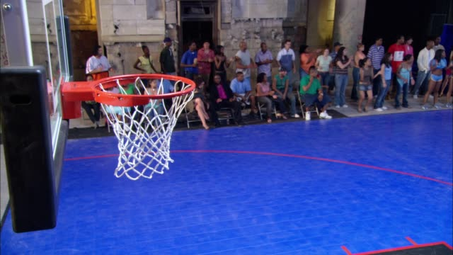 high angle down of basketball hoop above basketball court in makeshift gym or sports arena. crowds of men and women, spectators, cheerleaders at sideline. - makeshift stock videos and b-roll footage
