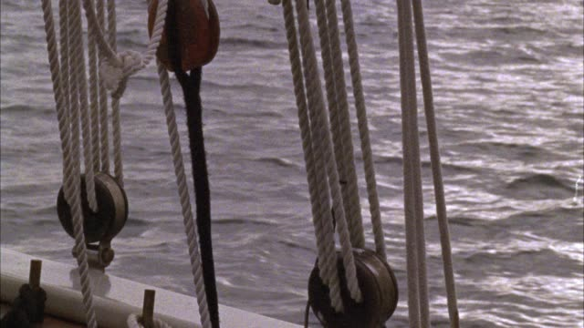 close angle of ropes or lines and pulleys on a sailboat. see deck of sailboat. see dark water moving left to right, could be ocean or sea. - rope stock videos & royalty-free footage