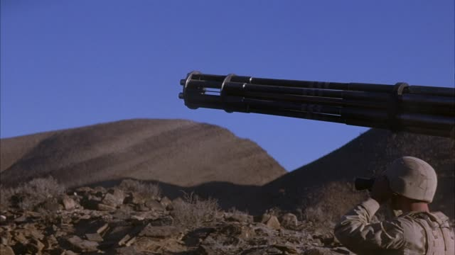 stockvideo's en b-roll-footage met medium angle of military soldier in desert fatigues or camouflage looking through black binoculars in parched desert with mountain in background. see six barrel machine gun in foreground. see machine gun barrels spin and move over pov. move with machine g - machinegeweer
