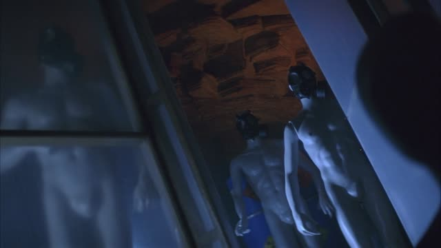 medium angle of mannequins wearing gas masks in possible military storage room or gas chamber. pov tilted in upwards angle. see mannequins standing inside glass room. see black design painted on ceiling. see blue metal containers or canisters behind manne - blue glass stock videos and b-roll footage