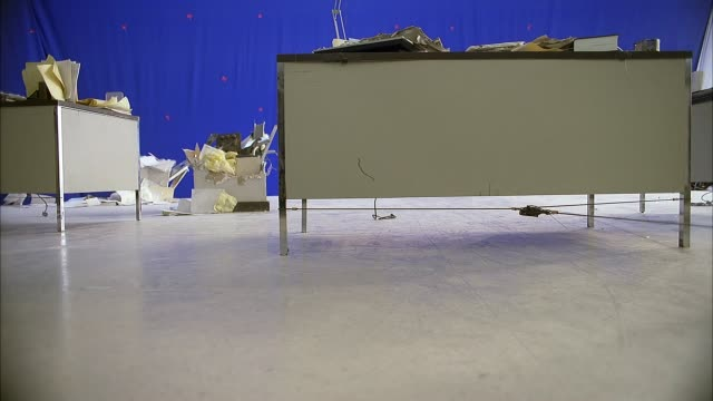 medium angle of desks covered in papers with blue screen in background. strong wind blows office furniture, rolling chair, woman across floor. camera moves forward, floor tilts as if collapsing. papers, chair fly past camera off edge of floor. telephone h - earthquake stock videos & royalty-free footage