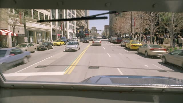 wide angle driving pov straight forward on city streets seen from bumpy cab of semi truck, eighteen wheeler or armored cars. pov moves periodically as if driver is looking in side view mirror. pedestrians, traffic and buildings in downtown area seen from - armored truck stock videos and b-roll footage