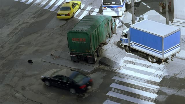 high angle down shows  intersection with dump truck and moving truck parked on sidewalk as speeding armored car crashes into sanitation vehicle, sending both flying. armored car has hole in roof. could be used for new york. taxis, cars, crosswalks also se - armored truck stock videos and b-roll footage