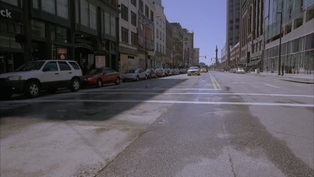 wide angle show from intersection shows oncoming traffic on city street as taxi, armored car then ups truck passes by. camera turns 180 degrees to show vehicles driving away. high rises, boarded up storefronts and parked cars line street in downtown area. - armored truck stock videos and b-roll footage