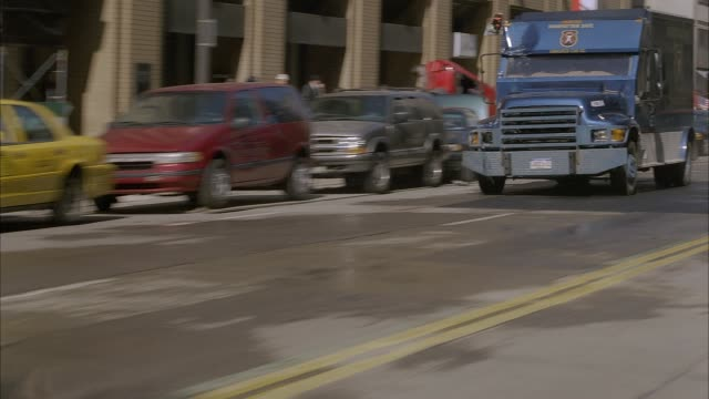 tracking shot follows blue armored car as it drives on cleveland city street, passing pedestrians on sidewalks, storefronts and parked cars, many of which are damaged. armored truck sideswipes three parked cars, crushing them, then drives past pov out of - armored truck stock videos and b-roll footage