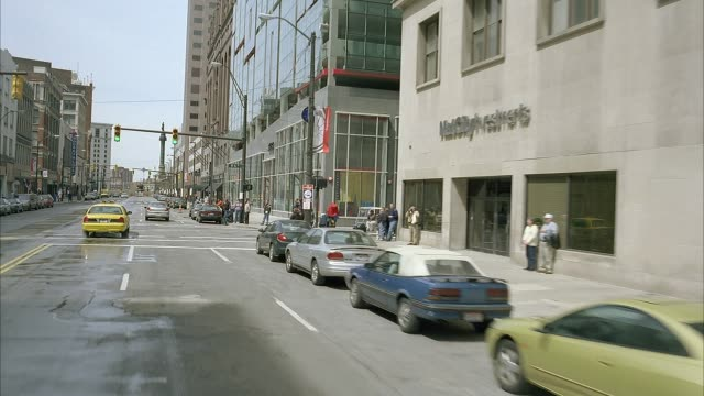 """wide angle driving pov straight forward through traffic on euclid ave in cleveland's warehouse district. soldiers' and sailors' monument seen in distance. pov turns right to show pedestrians on sidewalk, high rises, and storefronts. street sign """"w 6th st"""" - armored truck stock videos and b-roll footage"""