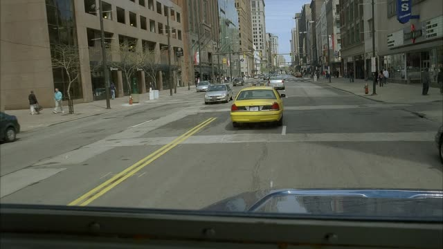 wide angle driving pov straight forward shows city street through window of blue semi truck, eighteen wheeler, or armored car. vehicle passes parked cars, sidewalks, pedestrians, high rise buildings, taxis, and traffic. could be downtown. - armored truck stock videos and b-roll footage