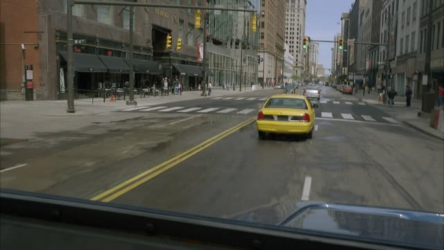 wide angle driving pov straight forward shows city street through window of blue semi truck, eighteen wheeler, or armored car. pov turns to left to show large window in door of vehicle. vehicle passes parked cars, sidewalks, pedestrians, high rise buildin - armored truck stock videos and b-roll footage