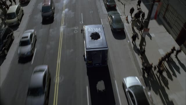 vídeos de stock, filmes e b-roll de high angle down moving pov shows armored car with hole in roof driving in traffic down euclid avenue in cleveland's warehouse district. pov moves down to follow behind armored car showing bags of money through back of truck. pedestrians walk on sidewalks - carro blindado