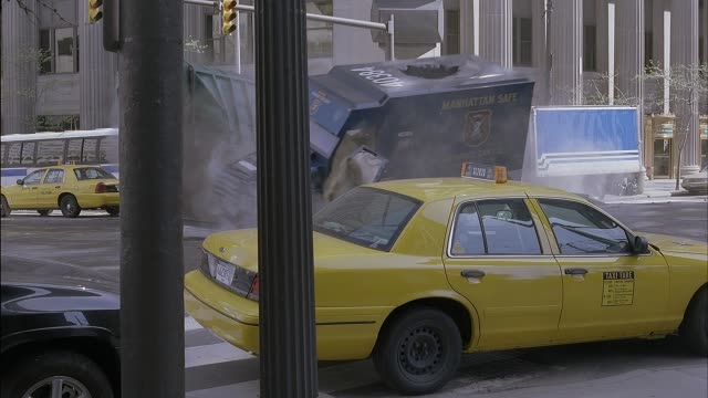 """wide angle of intersection, city streets with parked taxis, city bus and dump truck. several cars pass through intersection before blue armored truck with """"manhattan safe armored car co."""" on side crashes into sanitation truck. both vehicles lifted off gro - armored truck stock videos and b-roll footage"""