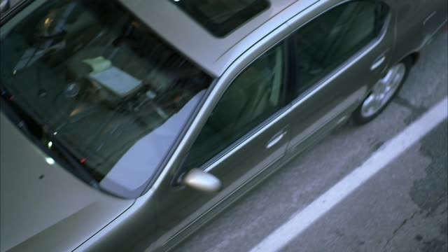 high angle down birdseye moving pov shows cars, traffic stopped in middle of city street. moves over woman exiting taxi holding cell phone, looking up at passing camera as if something is flying overhead. reactions. 60 fps. - 2006 stock videos & royalty-free footage