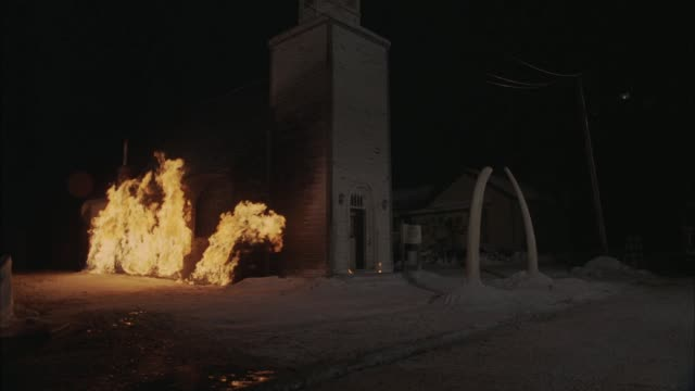 wide angle of wood frame church on fire, burning. flames shoot from base of church up sides. large wood column or steeple in front of building. snow, ice in fig. - steeple stock videos & royalty-free footage