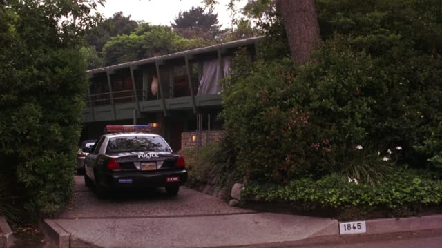 wide angle of upper class bungalow style house in hollywood hills. los angeles police car parked in driveway. house surrounded by tall trees, shrubs, and bushes. pan right to van parked on street beside driveway. - police car stock videos & royalty-free footage