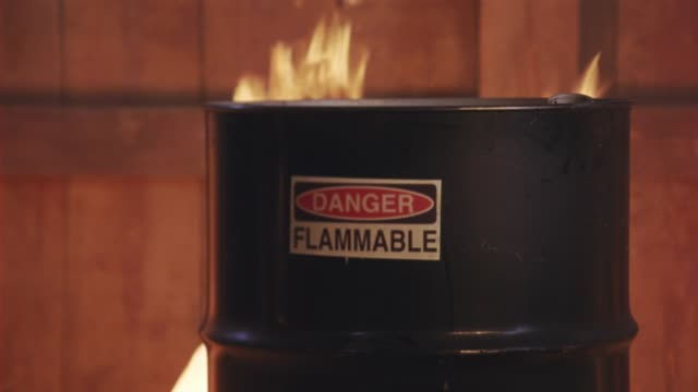 """vidéos et rushes de zoom in on """"danger flammable"""" sign on side of barrel that is about to be engulfed in flames and fire. could be barrel of gasoline. near explosions. - essence"""