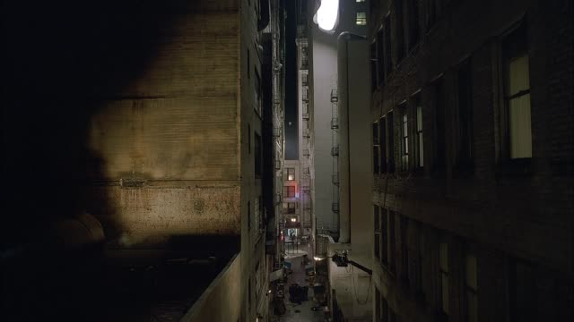 wide angle moving pov straight forward moves through narrow gap between upper floors of high rise apartment buildings showing dingy apartments, windows, fire escapes, and pipes. alley and new york city street also seen below. lower class. spidey-cam - fire escape stock videos & royalty-free footage