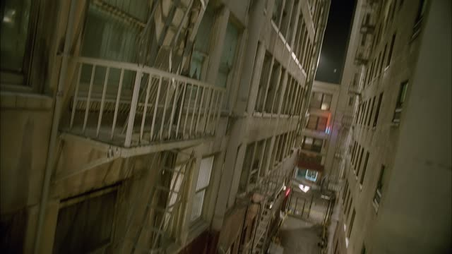 wide angle of narrow gap between upper floors of high rise apartment buildings shows dingy apartments, windows, fire escapes, and steam rising from pipes. pans down to show alley between buildings then back up repeatedly. could be pov of person on fire es - 屋根裏部屋点の映像素材/bロール
