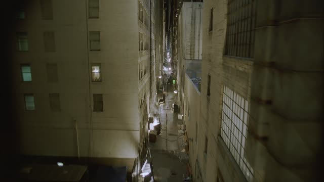 wide angle moving pov straight forward moves through narrow gap between upper floors of high rise apartment buildings showing apartments, windows, fire escapes, and pipes. alley and new york city street also seen below. brick buildings. lofts. lower class - narrow stock videos & royalty-free footage