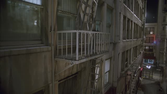 vidéos et rushes de pan up from fire escape outside dingy new york high rise apartment building to show ladder between floors then down to show alley between buildings. solitary man walks down street at end of alley. lower class. - échelle