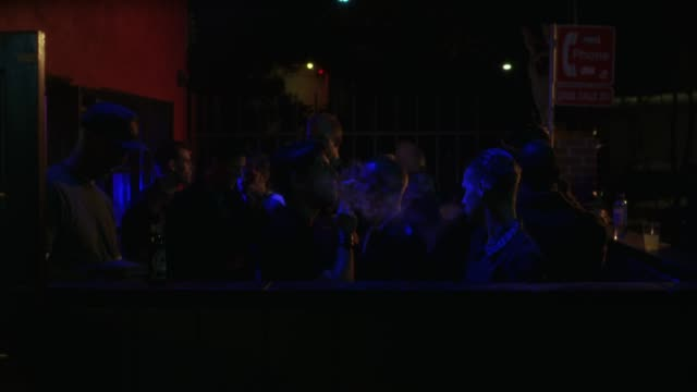 vídeos y material grabado en eventos de stock de medium angle of men smoking cigarettes and drinking outside of bar or club. pov pans left to bouncer checking id's at door. line of men waiting to enter club visible. could be used for west hollywood club. dance clubs. gay clubs. - west hollywood