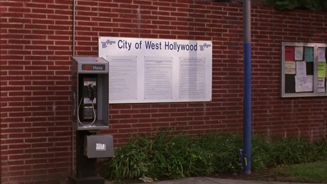 "vídeos y material grabado en eventos de stock de medium angle of ""city of west hollywood"" community center or municipal building. bulletin board is attached to brick building. pay phone in front of building. - west hollywood"