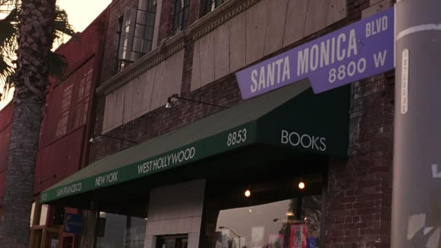 "MEDIUM ANGLE OF ""SANTA MONICA BLVD"" STREET SIGN ON A LIGHT POLE. BOOKSTORE AWNING VISIBLE IN BG. PALM TREE VISIBLE TO LEFT. HOLLYWOOD."
