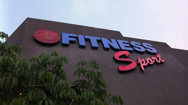 "medium angle of ""24 hour fitness sport"" neon sign. tree with leaves visible in fg. gyms. could be used for a gym in any location. - west hollywood stock videos & royalty-free footage"