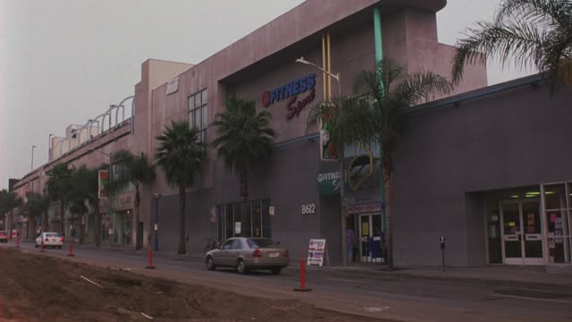 "wide angle of ""24 hour fitness sport"" neon sign. gym is on santa monica blvd. palm trees line sidewalk in front of gym. paved street is torn up for construction. - west hollywood stock videos & royalty-free footage"