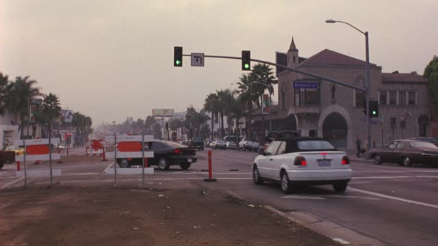 "wide angle of ""westbourne dr"" traffic signal off of santa monica blvd in west hollywood. cars drive in street. paved street is partially closed for construction in fg. church and palm trees visible beyond traffic signal. - west hollywood stock videos & royalty-free footage"