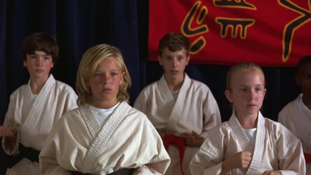 vídeos de stock, filmes e b-roll de medium angle pan left to right of children in a karate class. boys and girls in different belt colors perform karate warm ups. kids. martial arts. - karate