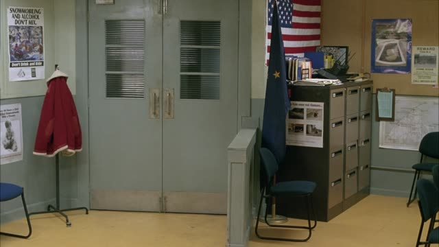 medium angle of police station office. american flag decorates wall and alaskan flag hangs from pole. could be used for any municipal building in alaska including a sheriffs office or city hall office. government buildings. - police station stock videos & royalty-free footage