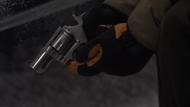 CLOSE ANGLE OF MAN HOLDING HAND GUN. WEARING GLOVES. SNUB NOSE REVOLVER COULD BE A MAGNUM.