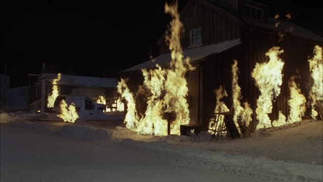 vídeos y material grabado en eventos de stock de wide angle of fires, flames, and smoke from burning wood cabin in small town or village. snow-covered street. - villa asentamiento humano